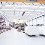 Eine Produktionshalle, an deren Decke Dunkelstrahler und Brennwerttechnik der Firma Schwank hängen.