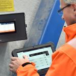 Ein Mann bedient die SchwankControl Touch Regelung für Hallenheizgeräte von Schwank.