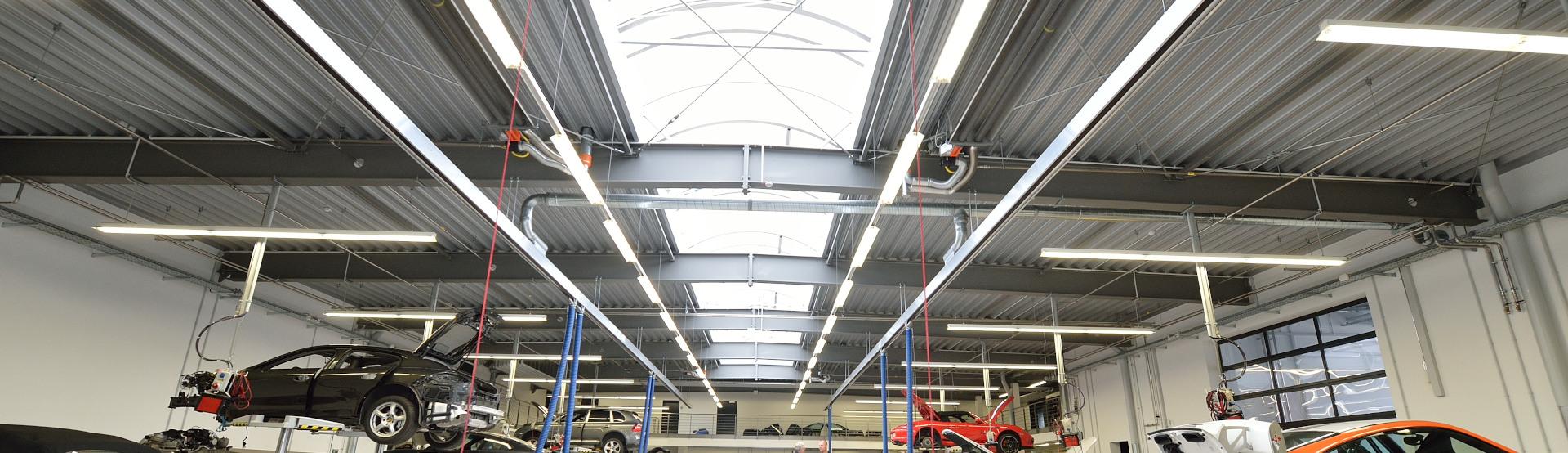 Schwank Dunkelstrahler hängen unter der Decke einer Porsche-Werkstatt.
